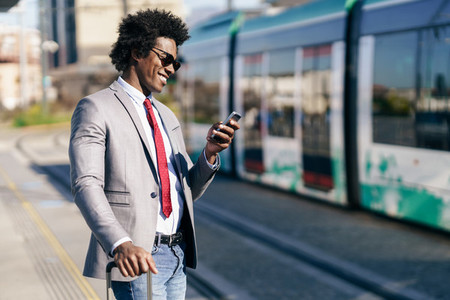 Smiling Black Businessman waiting for the next train