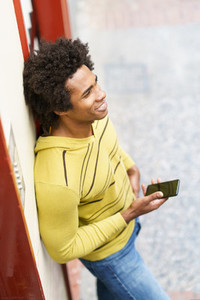Black man with afro hair and headphones using smartphone