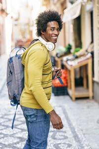 Black man with wireless headphones sightseeing in Granada