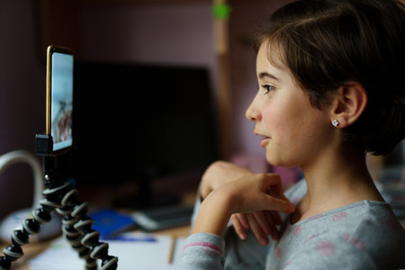 Little girls talking via video conference with smartphone