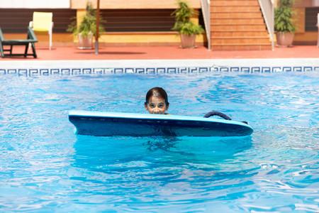 Cute girl playing with a bodyboard in a swimming pool