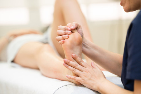 Medical massage at the foot in a physiotherapy center