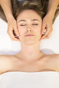 Young blond woman receiving a head massage in a spa center