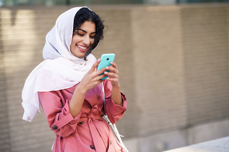 Young Arab woman wearing hijab texting message with her smartphone