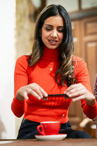 Arab young woman using smartphone in a cafe bar
