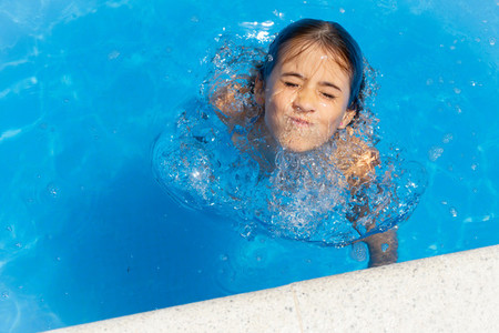 Cute girl eight years old playing in a swimming pool