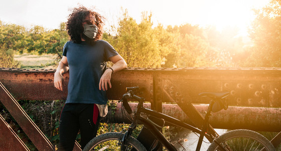 Man with surgical mask in the field with his bicycle