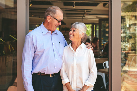 Senior couple standing at the entrance of their cafe