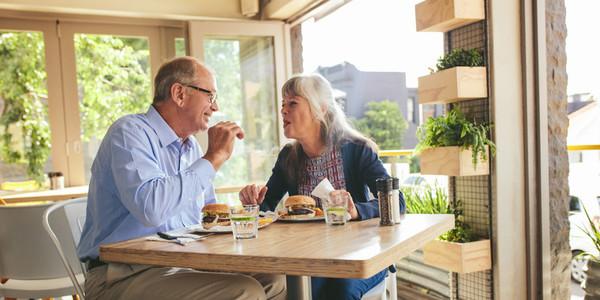 Senior couple enjoying eating burger together at a cafe