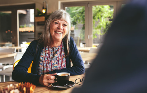 Happy mature woman at coffee shop