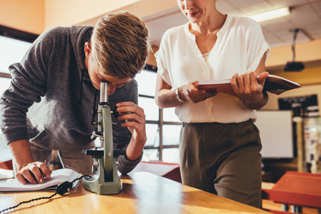 Student with teacher in school laboratory looking in microscope