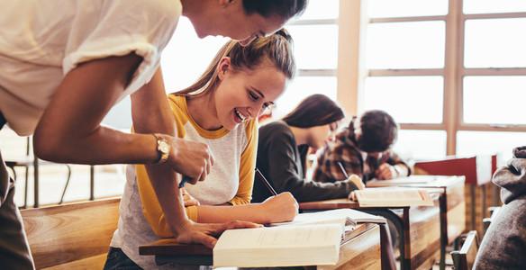 Girl attending a class being helped by her teacher