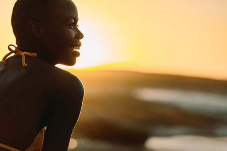Smiling african woman on the beach at sunset