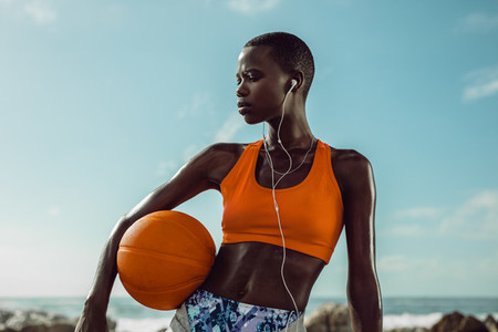 Woman with a basketball standing at the beach