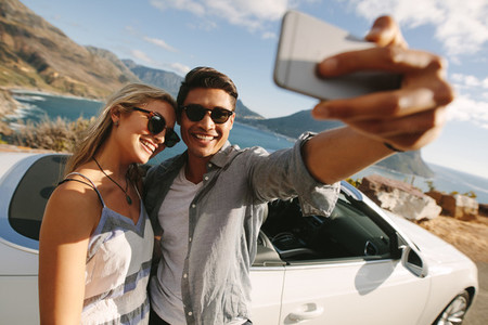 Man taking selfie with his woman on a road trip