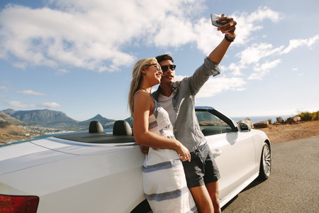 Beautiful couple taking pictures of themselves on road trip