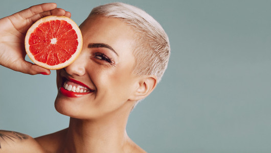 Beautiful woman holding a grapefruit