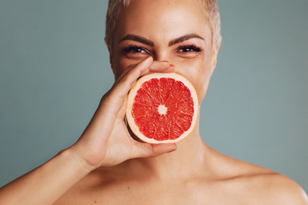 Woman holding a grapefruit against her mouth