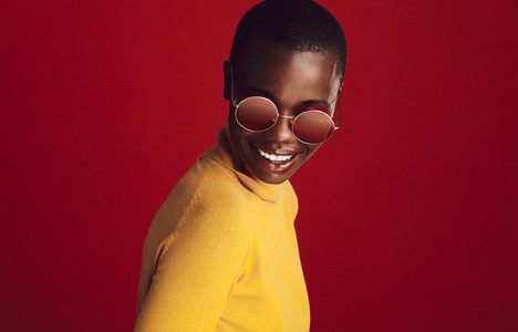 Fashionable woman in sunglasses on red background
