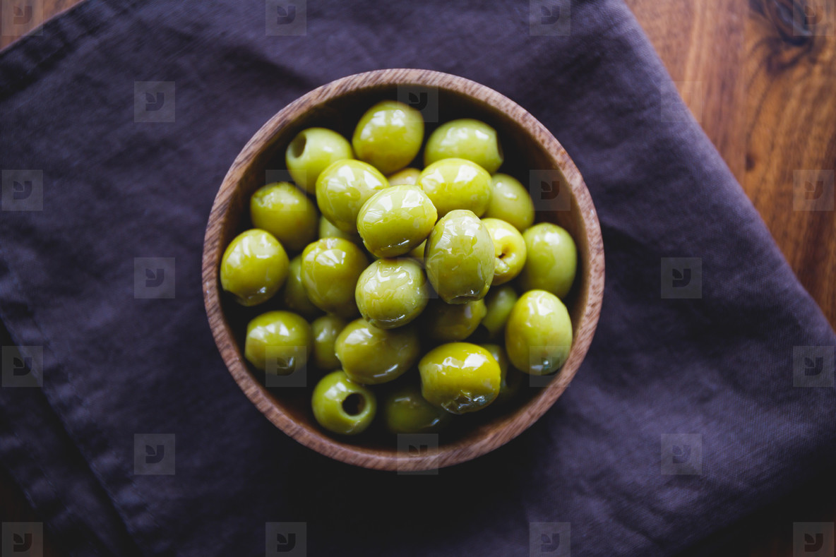 Green olives in a wooden bowl on a table  top view