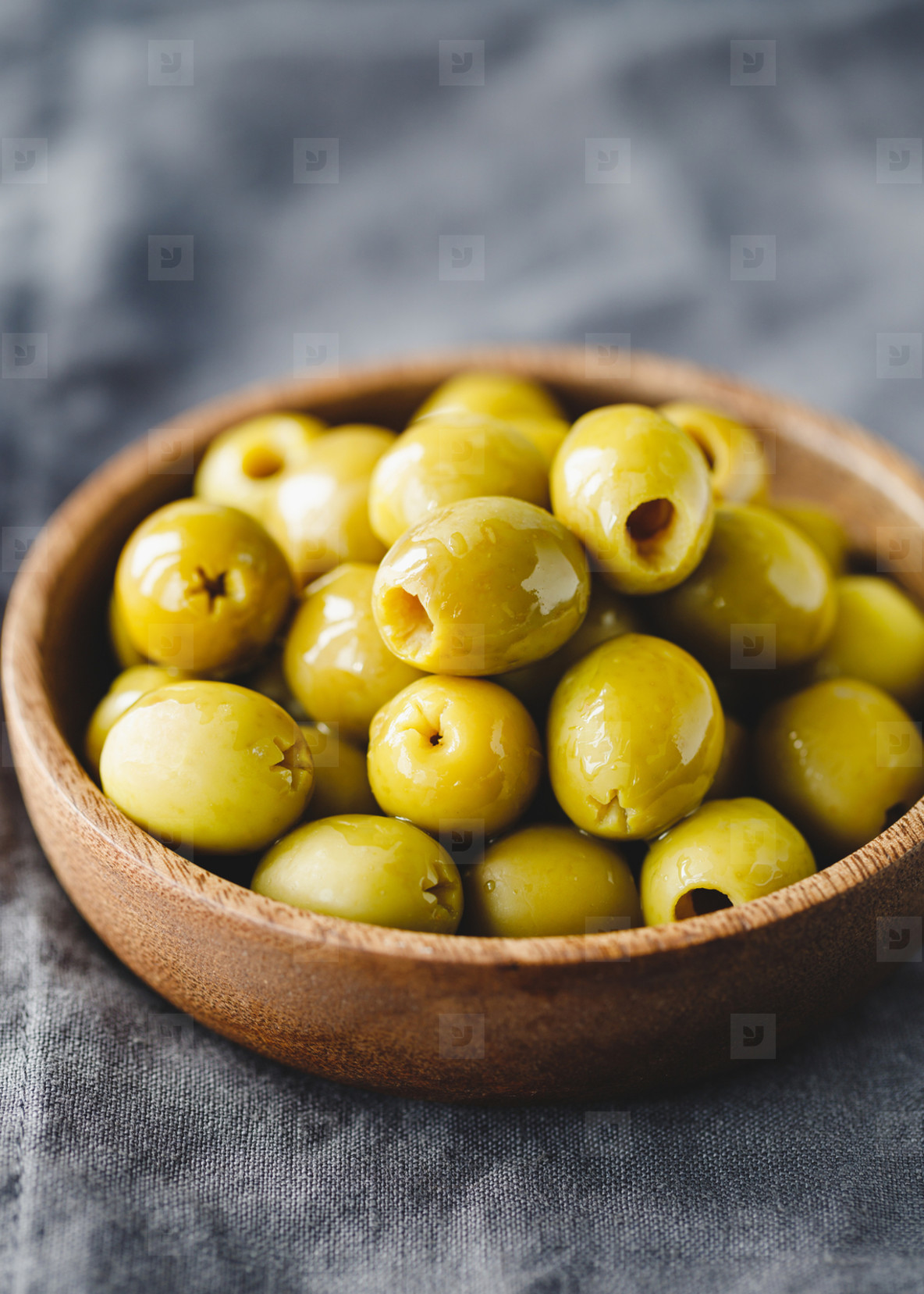 Green olives in a wooden bowl on a table  macro photography