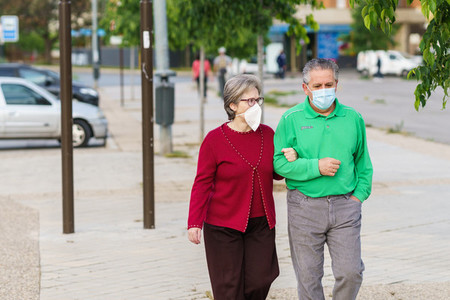 Senior couple taking a walk wearing masks to protect themselves from the coronavirus