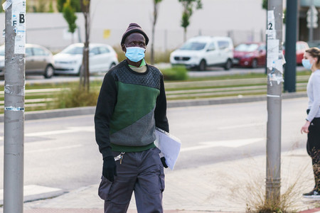Black man taking a walk wearing mask to protect him from the coronavirus