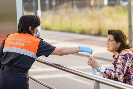 Civil protection woman handing out masks to protect against Covid 19