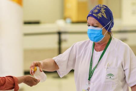 Woman pouring disinfectant gel on people entering the hospital