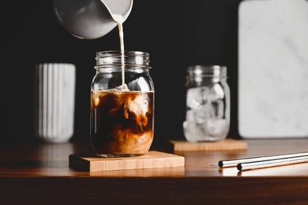Making iced latte  Pouring vegetarian soy milk into a glass jar with black coffee and ice cubes
