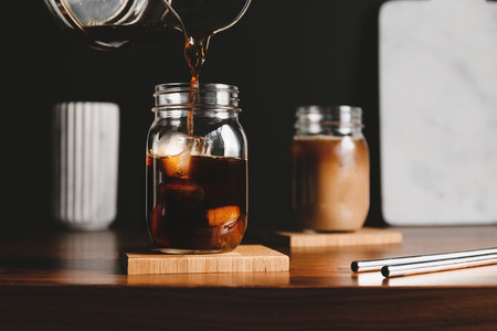 Making iced latte  Pouring black coffee into a glass jar with ice cubes