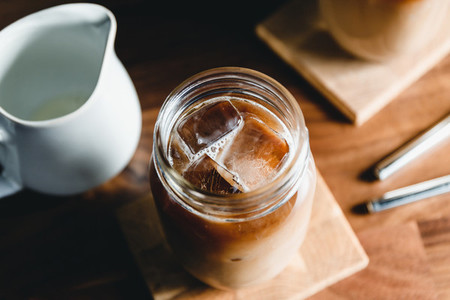 Top view of a glass jar with iced latte on a table