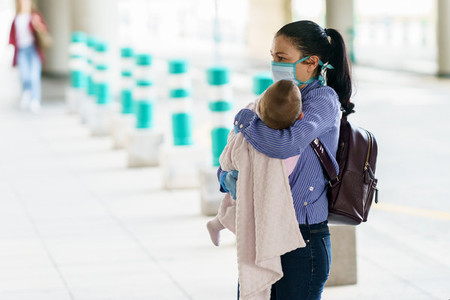 Woman protected by a mask taking her baby to the hospital