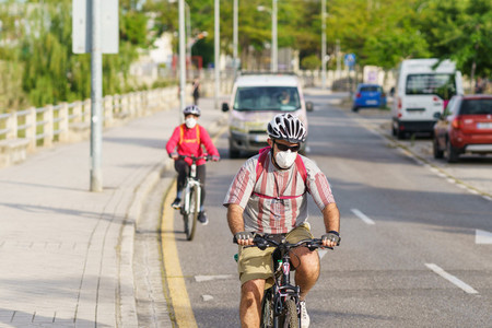 People riding bikes  wearing masks  as protection from the Covid 19 pandemic