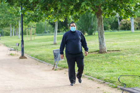 Fat man walking outdoors during the Covid 19 pandemic