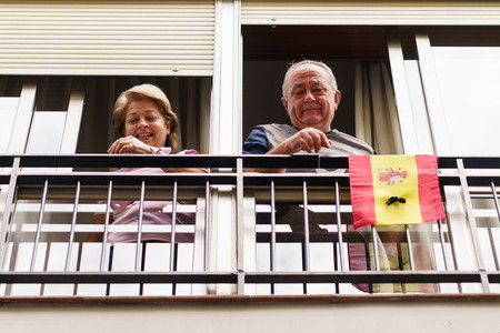 Older couple clapping in the window in support of people against the coronavirus