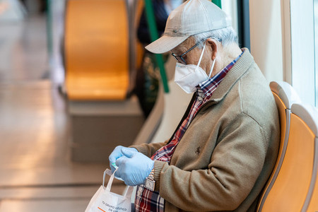 Senior man wearing surgical mask in the train during the Covid 19 pandemic