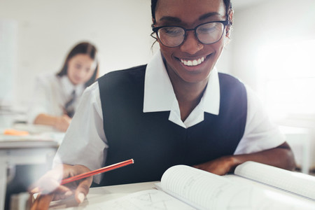 Female student smiling while studying in classroom