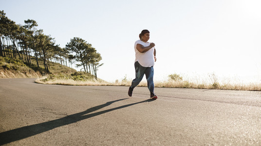 Overweight female jogging in morning