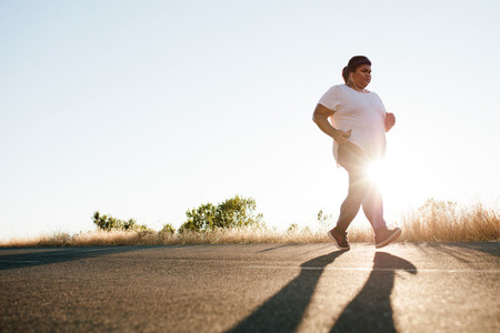 Overweight woman jogging on the highway