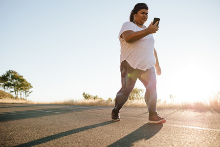 Overweight woman on power walk in morning