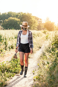 Young farmer woman walking with straw hat surgical mask and hoe