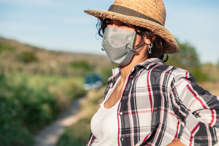 Young farmer woman with straw hat and surgical mask resting