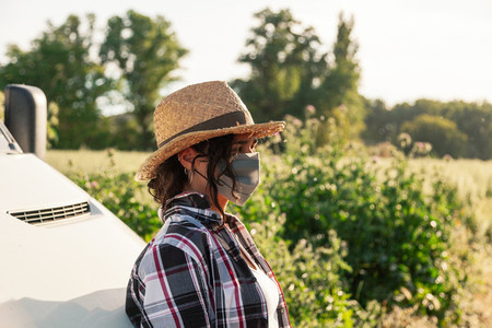 Young farmer woman with straw hat and surgical mask
