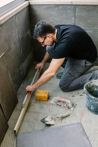 Bricklayer checking floor with a level