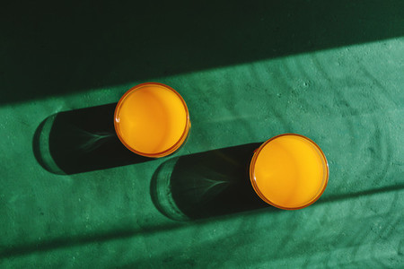 Summer creative photography with sunlight and shadows of orange juice