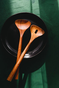 Wooden kitchen tools in a black plate over green background