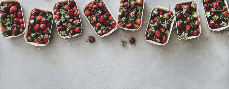 Fresh strawberries in plastic free boxes over grey background wide composition