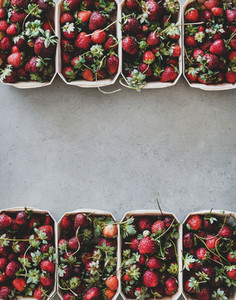 Fresh strawberries in plastic free boxes over concrete background copy space
