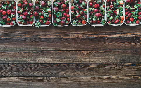 Fresh strawberries in plastic free containers over wooden background  copy space